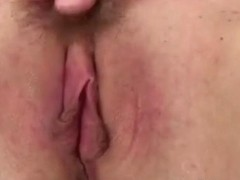 Rubbing her neatly shaven pussy