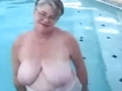 Corpulent granny in nylons plays in the pool