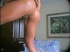 Tanned beauty puts dildo up her bum