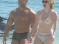 Naked couple enjoying themselves on the beach