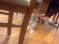 Candid mature barefeet in food court