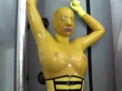 Hot girl in latex glamour yellow catsuit gets to climax