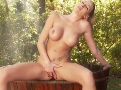 A busty blonde fingers her pussy outdoors