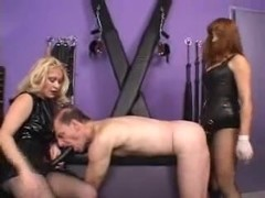Two dominatrices fuck a sissy thrall in the butt