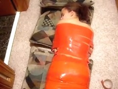 Young brunette laying on the floor wrapped in red tape