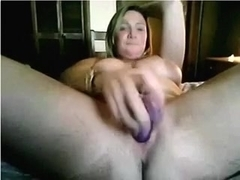 Big tit woman penetrates her fanny with her large plastic fake dick