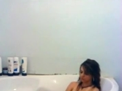 girl masturbates with the showerhead in the bathtub