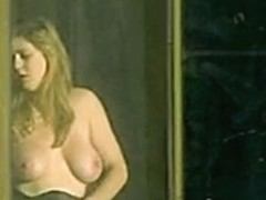 Big tits girl getting dressed by the window