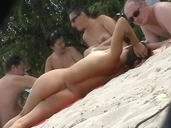 Naked people are relaxing on the beach and filmed