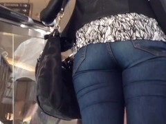 Denim jeans ass going up the escalator
